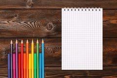 Un bon nombre de stylos et de crayons de marqueur assortis de couleurs avec le carnet Image stock