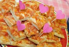 un bon nombre de tranches de pizza avec les drapeaux en forme de coeur Images stock