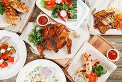 Un bon nombre grillés de nourriture Servir sur un conseil en bois sur une table rustique Menu de rôtisserie, une série de photos  Image stock