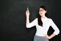 Un bon professeur asiatique enseignent sur le tableau noir avec la craie photos stock