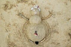 Un bonhomme de neige du sable et coquillages sur une plage Photos libres de droits