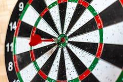 Un bordo rotondo per il gioco dei dardi vicino su, un dardo rosso ha colpito l'obiettivo fotografia stock