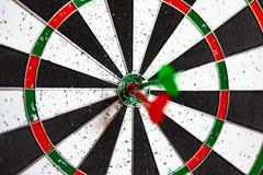 Un bordo rotondo per il gioco dei dardi vicino su, dardi rossi e verdi ha colpito l'obiettivo immagini stock libere da diritti