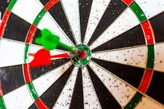 Un bordo rotondo per il gioco dei dardi vicino su, dardi rossi e verdi ha colpito l'obiettivo fotografia stock libera da diritti