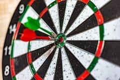 Un bordo rotondo per il gioco dei dardi vicino su, dardi rossi e verdi ha colpito l'obiettivo fotografie stock libere da diritti
