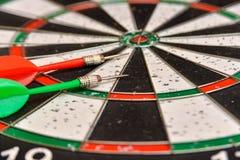 Un bordo rotondo per il gioco dei dardi vicino su, dardi verdi e rossi è sull'obiettivo fotografia stock