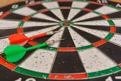 Un bordo rotondo per il gioco dei dardi vicino su, dardi verdi e rossi è sull'obiettivo immagine stock