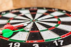 Un bordo rotondo per il gioco dei dardi vicino su, dardi verdi e rossi è sull'obiettivo immagini stock