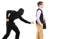 Un borsaiolo con la mascherina che prova a rubare un raccoglitore Fotografia Stock