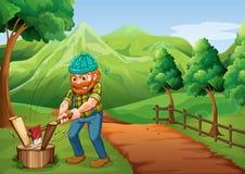 Un boscaiolo che taglia il legno a pezzi alla via che va all'azienda agricola Fotografia Stock