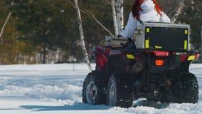 Un bosque del invierno en el tiempo del d?a Una mujer con moto de nieve que monta del pelo del jengibre en el tiempo del d?a Visi almacen de video
