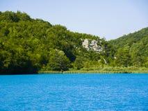 Un bosque y un lago con una roca imágenes de archivo libres de regalías