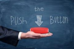 Un botón rojo grande que descansa sobre la palma del ` s del hombre de negocios debajo de un dibujo de la pizarra que dice empuje Fotografía de archivo libre de regalías