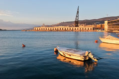 Un bote pequeño amarró en el puerto de Trieste antes de la puesta del sol Imagen de archivo libre de regalías