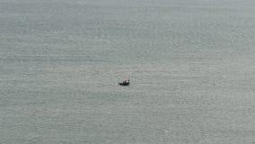 Un bote pequeño con un pescador en el medio de un océano enorme metrajes