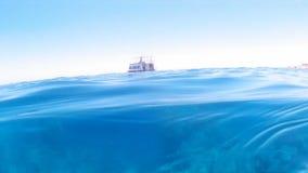 Un bote pequeño en las ondas azules del océano almacen de video