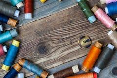 Un bottone d'annata e bobine dei fili differenti Fotografia Stock