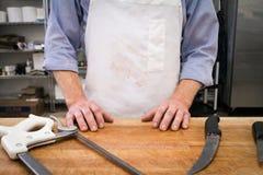 Un boucher pose derrière ses outils et bloc Photos stock