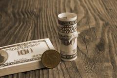 Un bouchon de cent billets de banque du dollar et une pièce de monnaie d'un dollar de prochain Photographie stock libre de droits