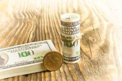 Un bouchon de cent billets de banque du dollar et une pièce de monnaie d'un dollar de prochain Photos stock
