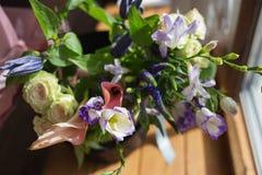 Un bouquet étonnant de différentes fleurs colorées se tenant près de la fenêtre Images libres de droits