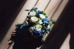 Un bouquet d'une jeune mariée avec les fleurs bleues se trouve sur le plancher Photo stock