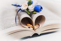 Un bouquet de la jeune mariée des roses et des anneaux de mariage blancs et bleus de l'or photographie stock libre de droits