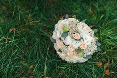 Un bouquet de la jeune mariée du blanc et des roses de laiterie sur une fin d'herbe  Bouquet nuptiale photos libres de droits