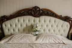 Un bouquet de mariage des roses blanches et des orchidées blanches se tient à la tête du lit Photo stock