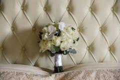 Un bouquet de mariage des roses blanches et des orchidées blanches se tient à la tête du lit Fin vers le haut Image libre de droits