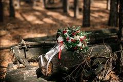 Un bouquet de mariage des roses blanches et rouges se trouve sur des identifiez-vous la lumière du soleil Images stock