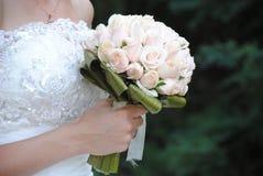 Un bouquet de mariage des roses dans les mains d'une jeune mariée en gros plan Photographie stock libre de droits