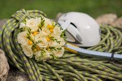 Un bouquet de mariage fait de roses blanches sur une corde avec une hache de glace Photo libre de droits