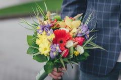 Un bouquet de ressort fleurit dans une main du ` s d'homme Photos libres de droits