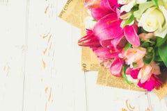 Un bouquet des fleurs d'un lis, d'un gerbera, des roses blanches et d'un alstroemeria sur une table en bois blanche Des vacances, Photos stock