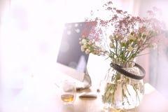 Un bouquet des fleurs dans un vase rond sur une table par la fenêtre Un ordinateur Lieu de travail à la maison Fond avec des coul Photos libres de droits