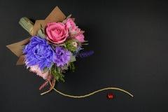Un bouquet des fleurs de papier colorées et un petit coeur rouge sur un fond noir comme contexte pour une carte postale, lettre d Photos libres de droits