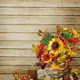 Un bouquet des fleurs, des feuilles et des baies dans un panier en osier sur un fond en bois illustration libre de droits