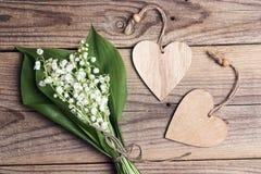 Un bouquet des fleurs du muguet avec en bois entend sur le vieux fond en bois de table photos stock