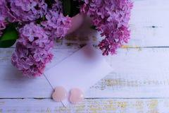 Un bouquet des fleurs lilas sous un vase lilas et une enveloppe avec un endroit pour une inscription postcard photos stock