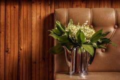 Un bouquet des lis sauvages de la vallée dans une vieille théière sur le fond en bois Image stock