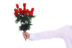 Un bouquet des roses dans une main masculine sur le blanc Photographie stock