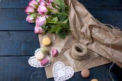 Un bouquet des roses est rose, aux coeurs de papier et blancs gris Macarons doux de pâtes de différentes couleurs, le jour du ` s Images stock