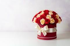 Un bouquet des roses roses et blanches décorées dans une boîte de chapeau sur un fond clair Images libres de droits
