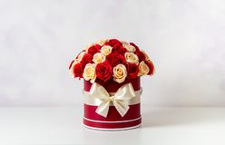 Un bouquet des roses roses et blanches décorées dans une boîte de chapeau sur un fond clair Photos libres de droits