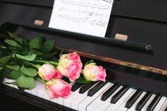 Un bouquet des roses et des notes roses sur le clavier de piano Photos libres de droits
