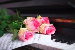 Un bouquet des roses et des notes roses sur le clavier de piano Photographie stock