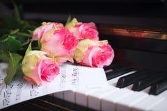 Un bouquet des roses et des notes roses sur le clavier de piano Image libre de droits