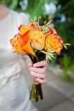 Un bouquet des roses oranges et d'un koala de mariage, dans les mains de la jeune mariée Photographie stock