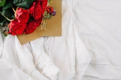 Un bouquet des roses rouges, enveloppe avec la félicitation sur un fond de toile Photo libre de droits